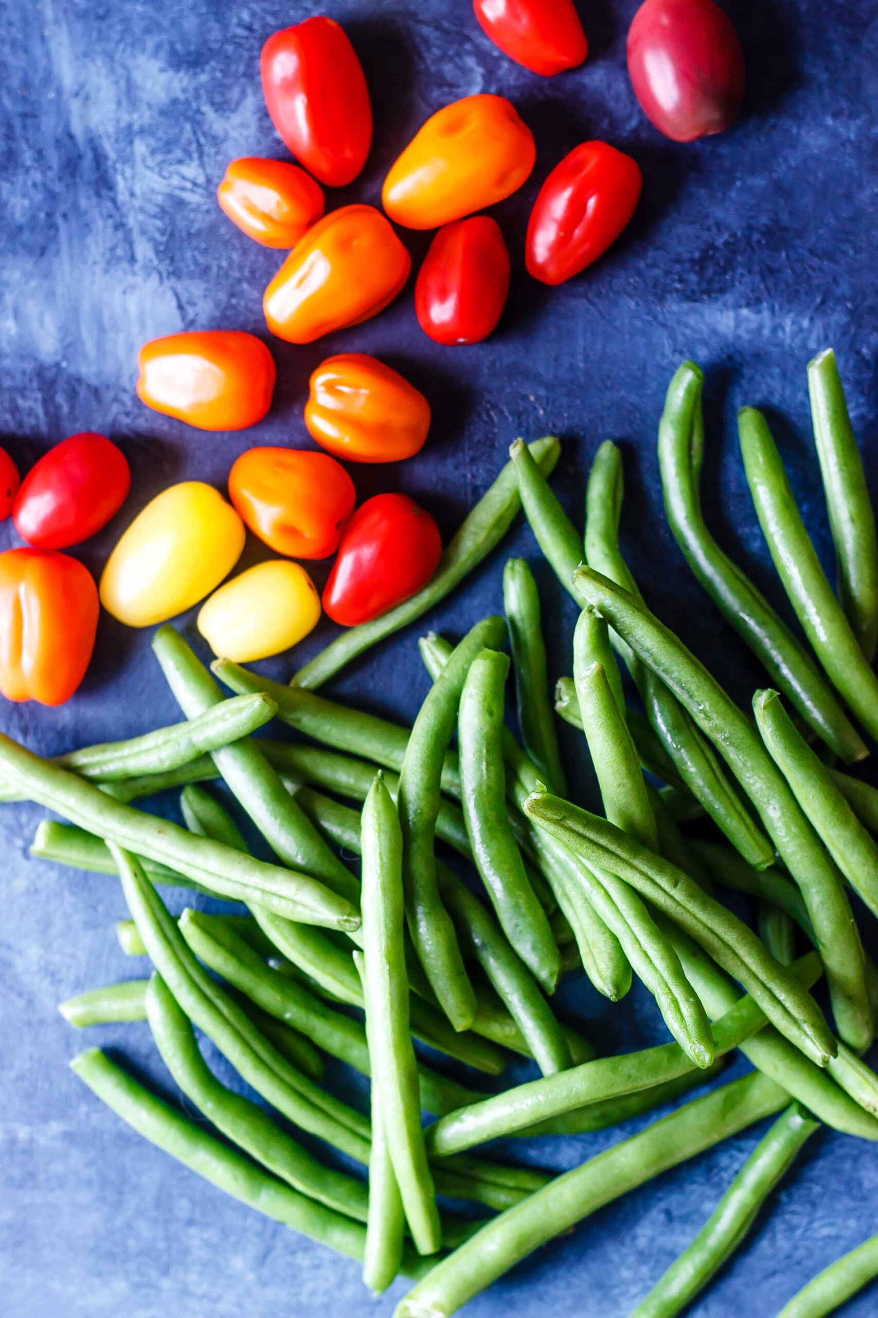 Green Beans and Cherry Tomatoes on a blue background