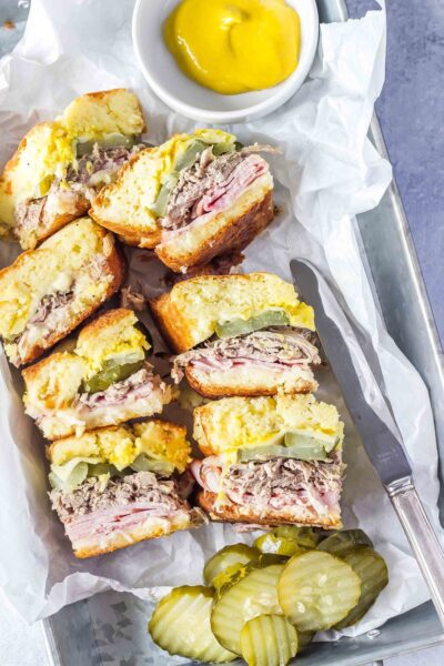 Keto Cuban Sliders in a tray with white parchment paper, pickles and mustard on the side