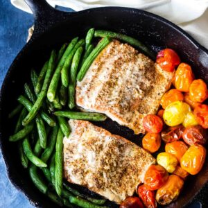 Salmon with Burst Tomatoes and Green Beans in cast iron skillet on table