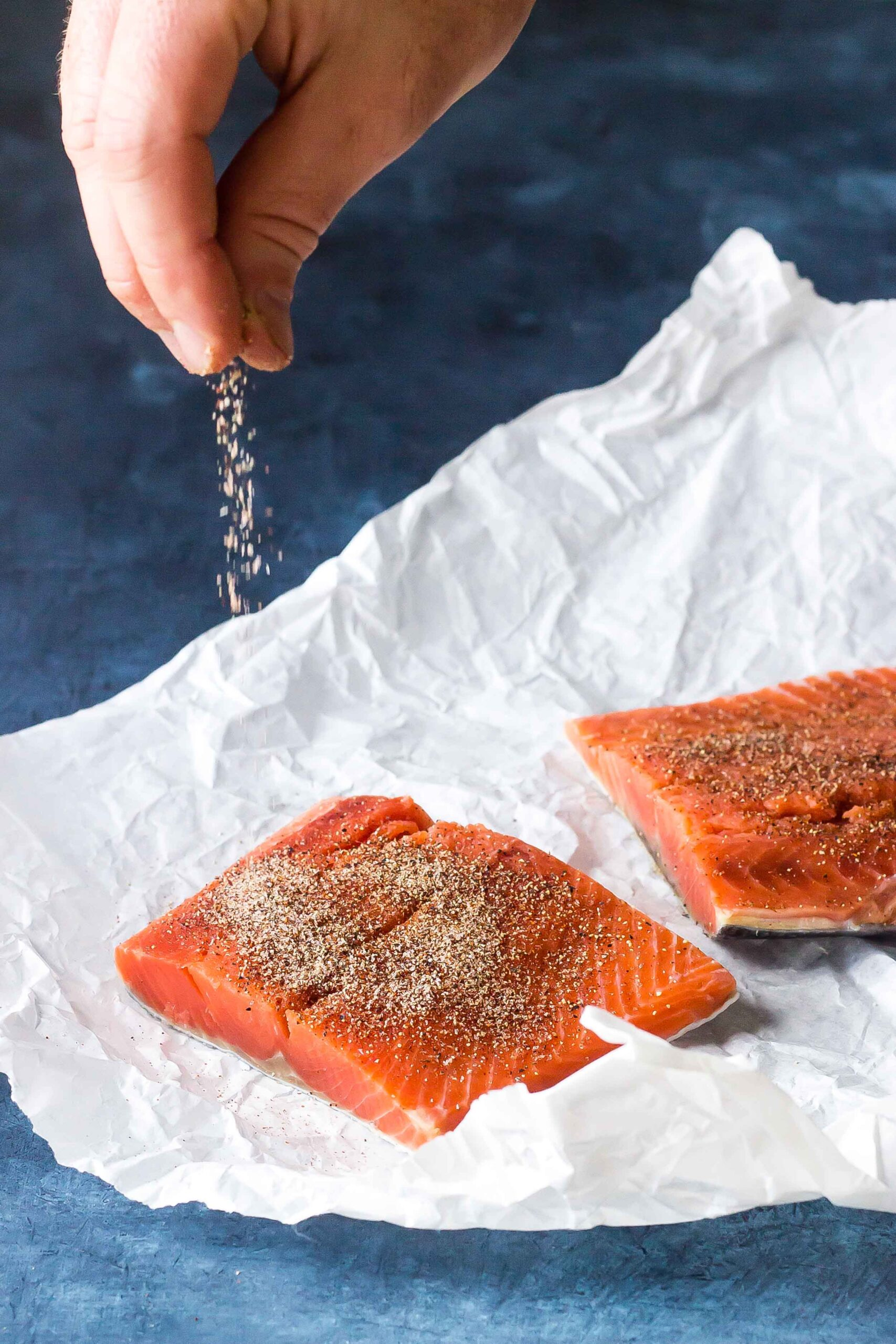 salmon fillets on parchment paper being seasoned