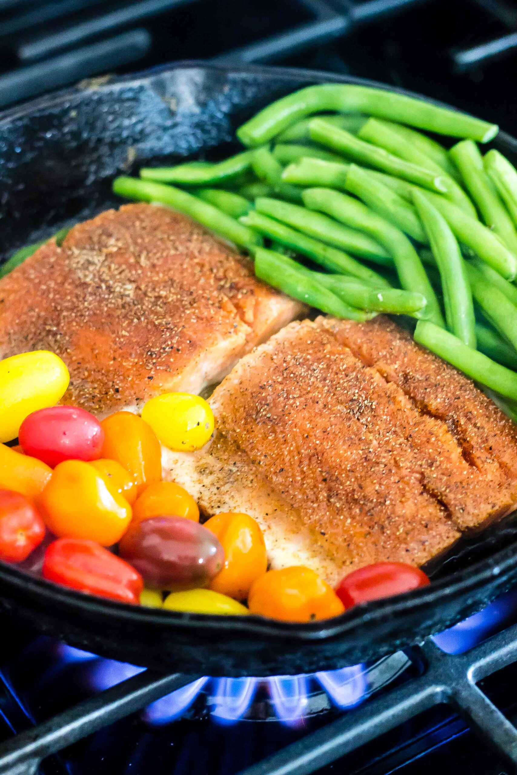 salmon with burst tomatoes and green beans in skillet on stovetop