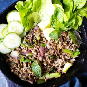 Keto Larb in a cast iron skillet on a blue background