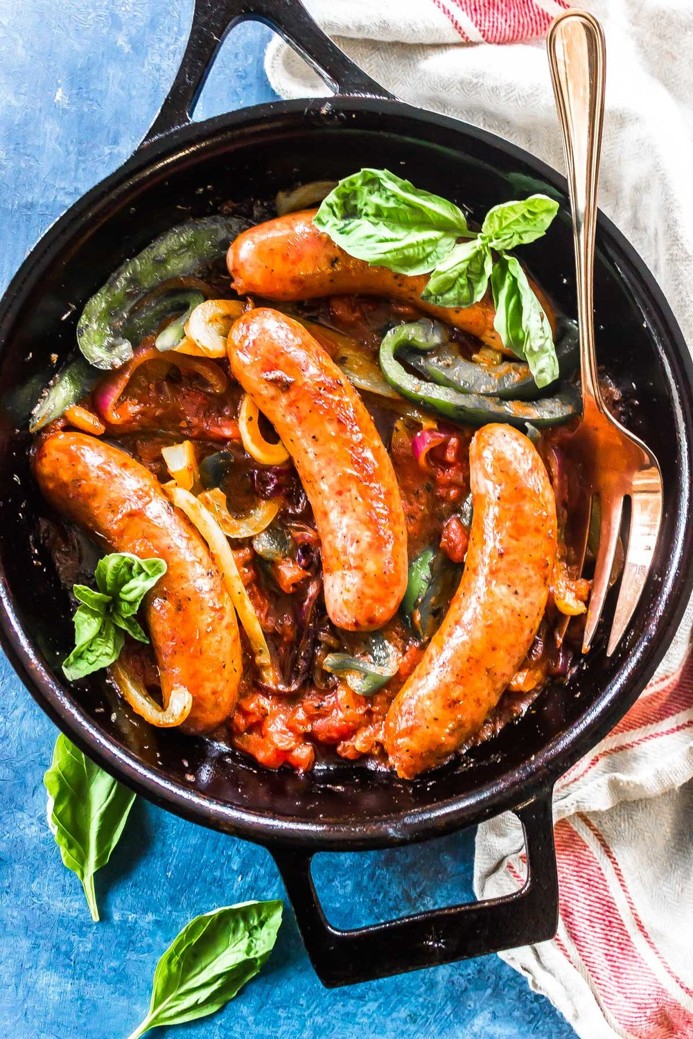 Keto Italian Sausage, Peppers, and Onions in a cast iron skillet with fresh basil.