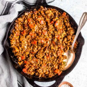 Keto Sloppy Joe mixture in a cast iron skillet with a serving spoon