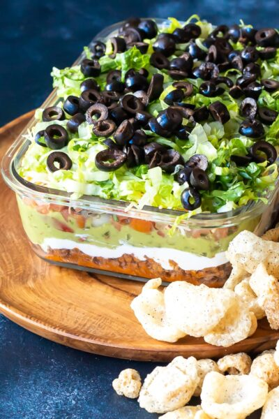 Keto 7 Layer Taco Dip in glass bowl showing the layers with pork rinds scattered around