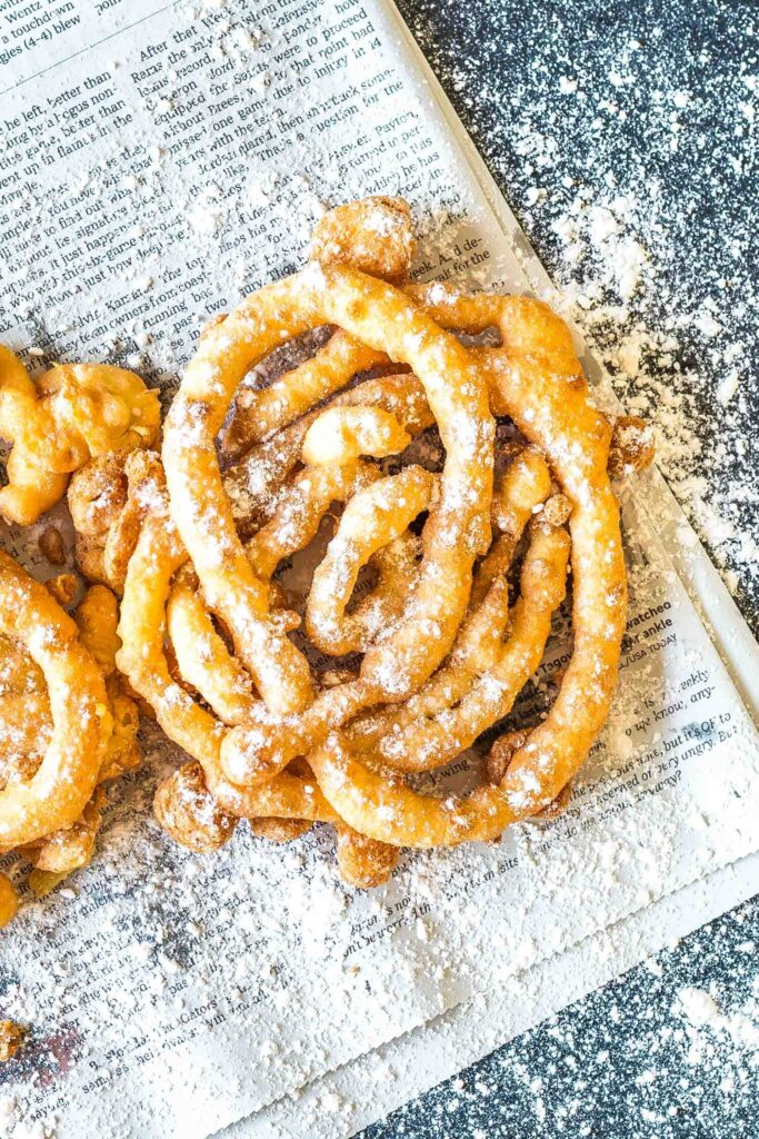 Keto Funnel Cake on a newspaper sprinkled with powdered erythritol