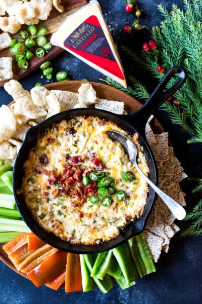 Spicy gouda bacon dip in a skillet on a platter surrounded by pork rinds and vegetable sticks.