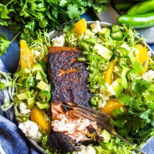 Cajun Salmon with Avocado Orange Salad o n a blue background