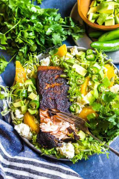 Cajun Salmon with Avocado Orange Salad o n a blue background