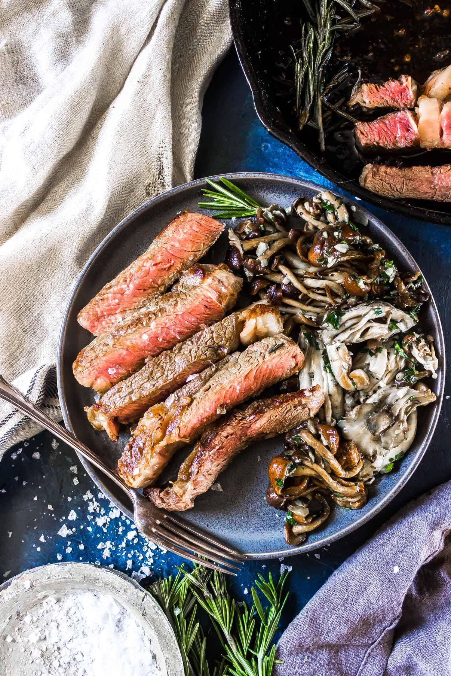 Cast Iron Steak on a plate with Garlic Butter Mushrooms