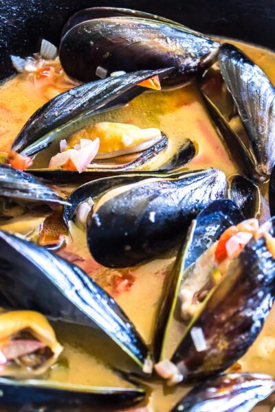 closeup image of Chilli Mussels simmering in a cast iron skillet