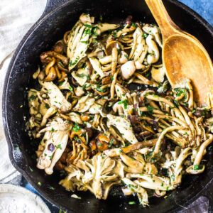Garlic Butter Mushrooms in a cast iron skillet with a wooden spoon