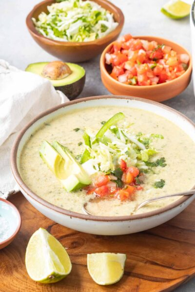 Keto Chile Relleno Soup in bowl with pico de gallo, shredded cabbage, and avocado as the toppings