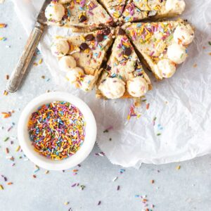Keto Confetti Skillet Cookie on parchment with sprinkles scattered around