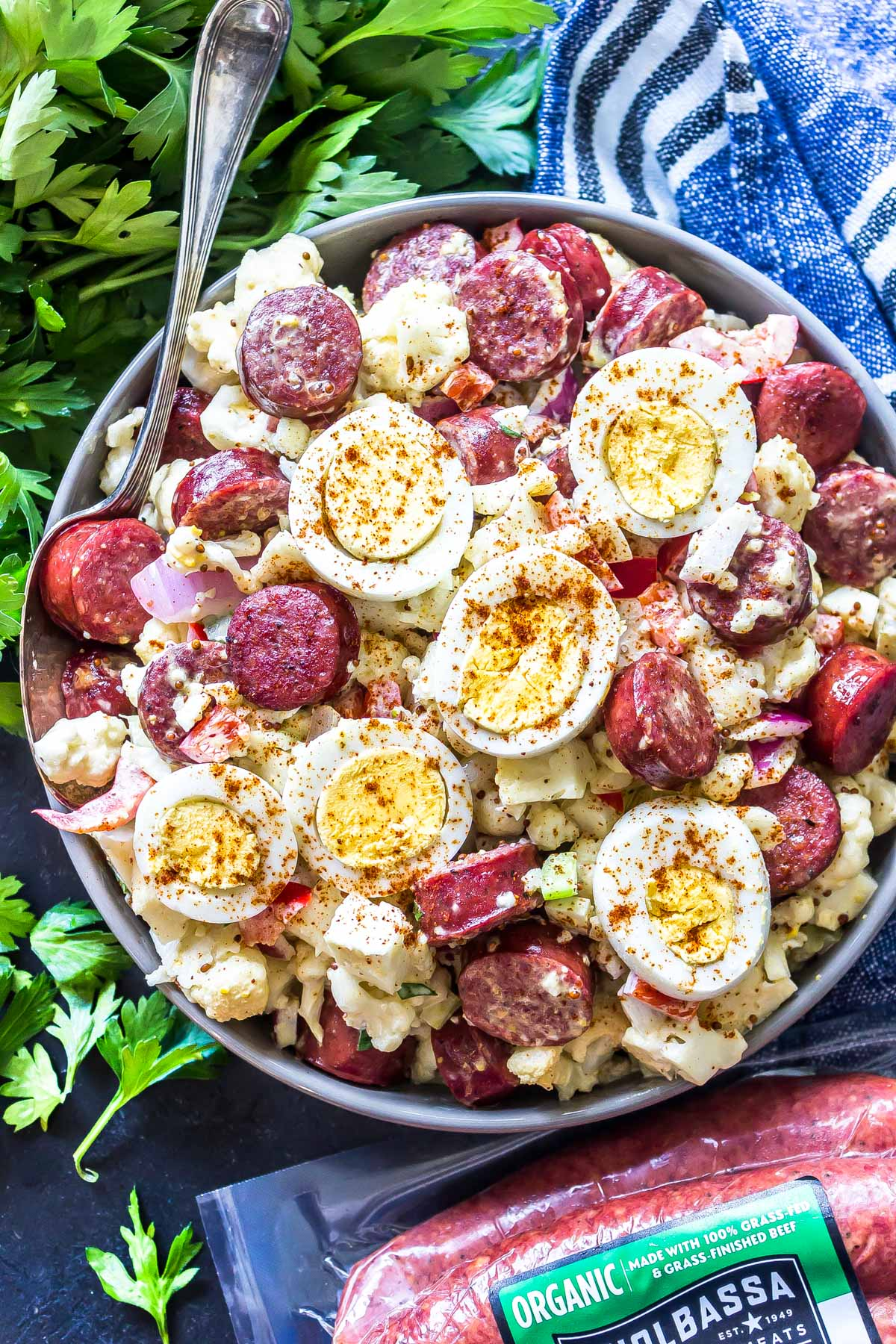"Keto ""Potato"" Salad with Smoked Sausage In a large serving bowl with kiolbassa packaging in the foreground."