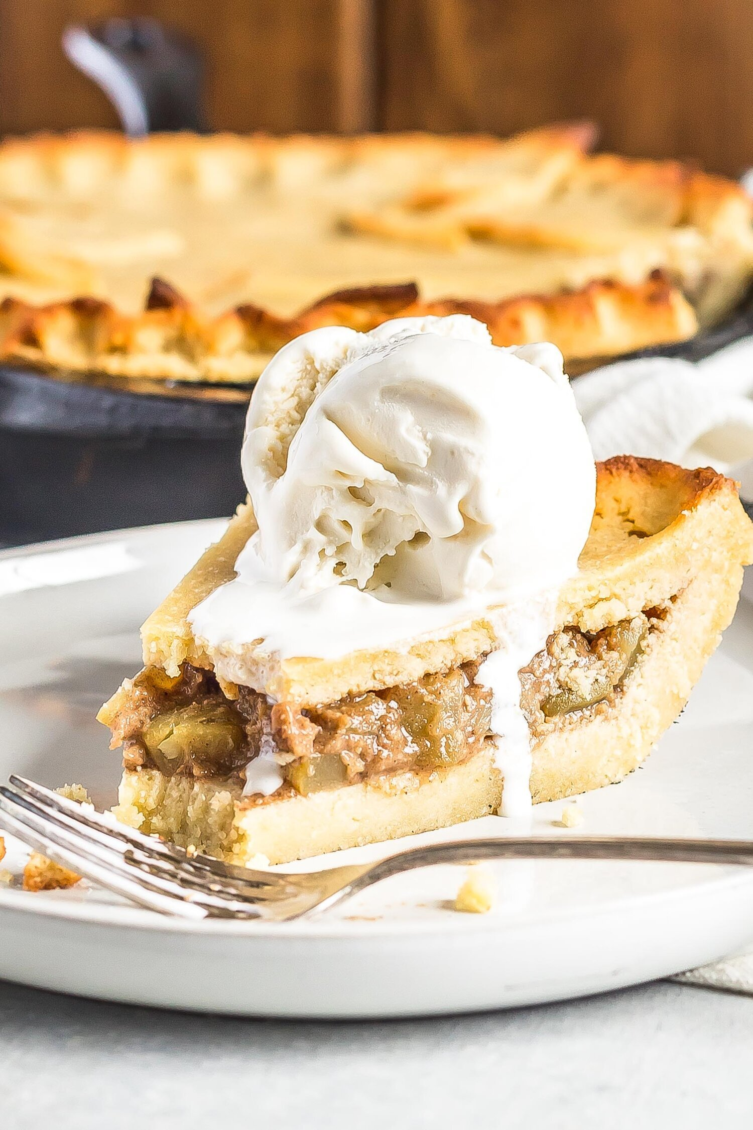 A slice of Keto Apple Pie with Ice cream on top served on a plate. Skillet in the background