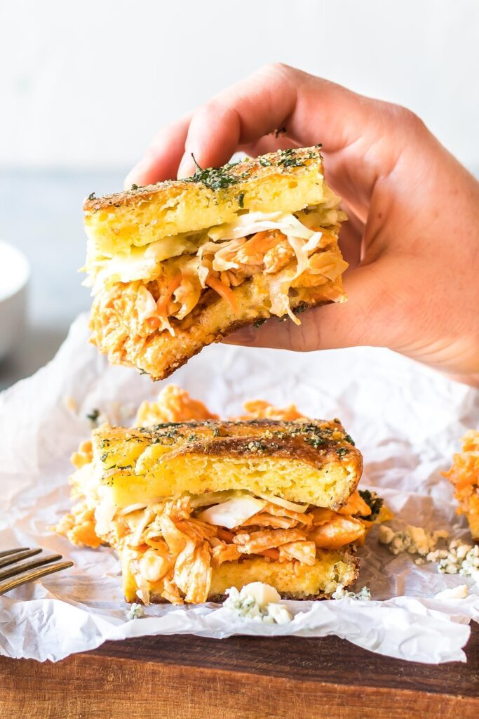 Keto Buffalo Chicken Sliders. One a piece of white parchment paper, another being held in hand.