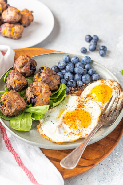 Keto Breakfast Meatballs on plate with eggs and blueberries