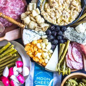How To Build a Keto Cheese Board featured image with a huge spread of different cheeses, dips, crackers/pork rinds, veggies and berries