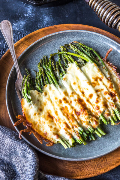 Easy Keto Cheesy Asparagus on a grey plate on a wooden charger.