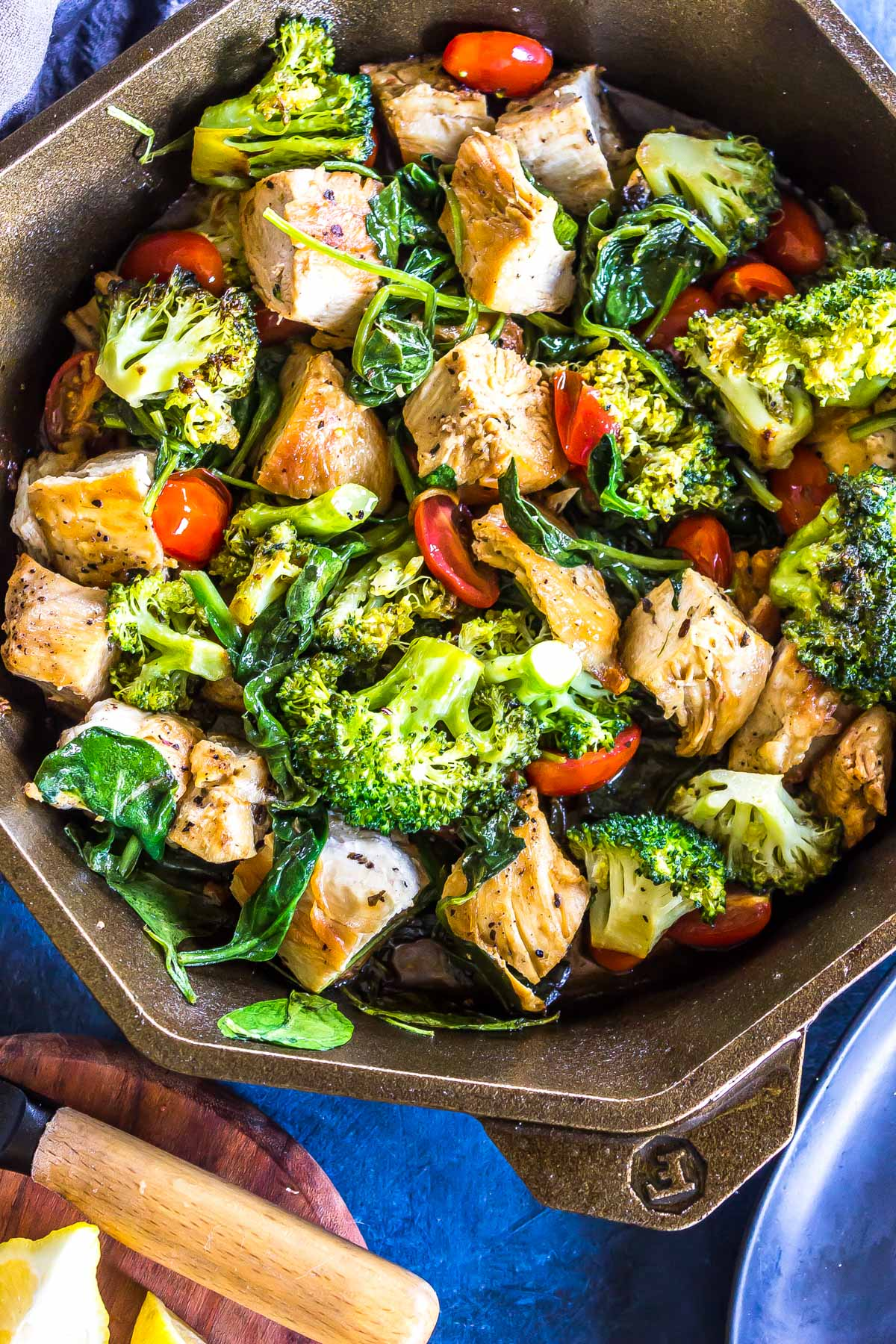 Close up: Keto Italian Chicken Skillet (cubed chicken, broccoli, cherry tomatoes and sauce) in a finex cast iron skillet.