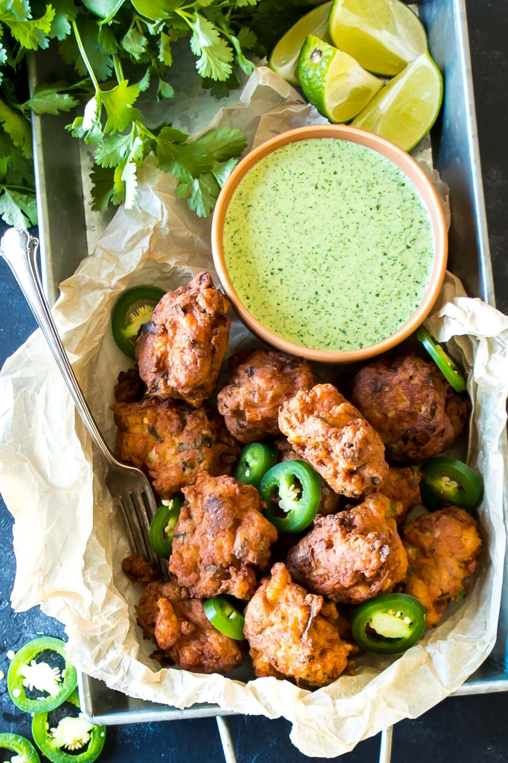 Top-down of Keto Hushpuppies in a tray, with a bowl jalapeno sauce directly behind
