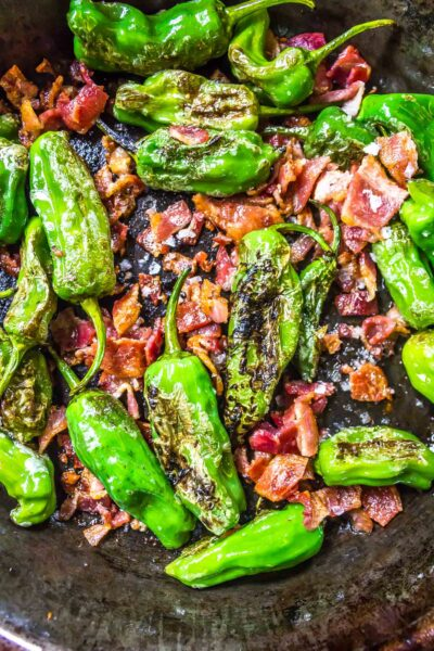Keto Shishito Peppers in a skillet with bacon