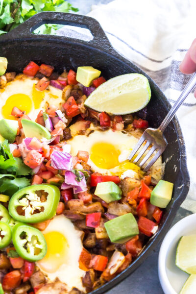 Keto Southwestern Breakfast Hash with a fork taking a bite out of a runny egg