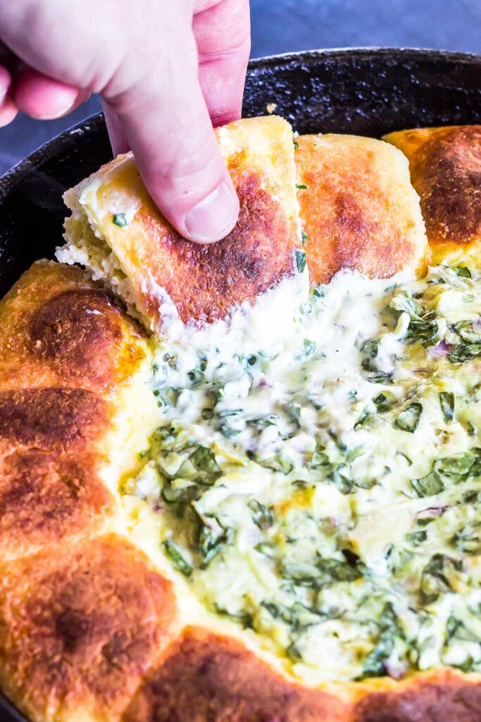 Keto Spinach Artichoke Dip Pull Apart Rolls with one being pulled out of skillet