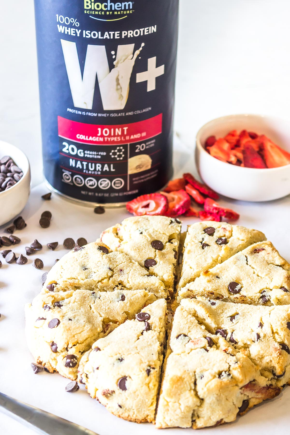 Strawberry Chocolate Chip Scones flanked by chicolate chips and dehydrated strawberries with a Cannister of Biochem Whey protein isolate plus joint powder prominently featured