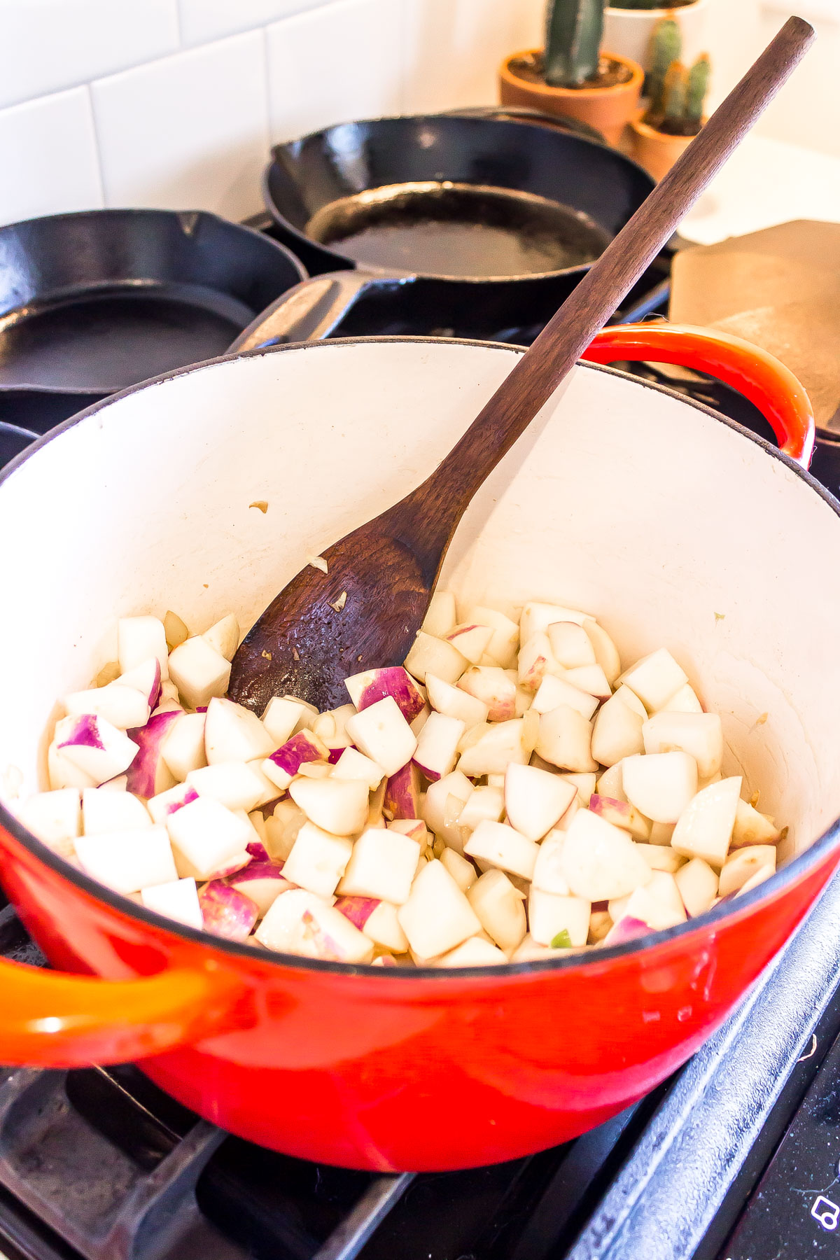 Cut turnips in a large dutch oven atop a gas range