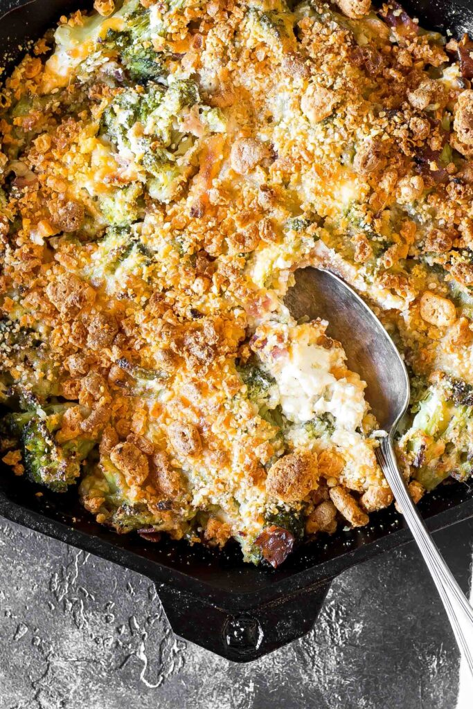 Cheesy Keto Broccoli Casserole in a cast iron skillet with a serving spoon preparing to scoop