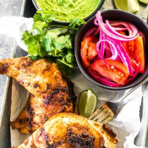 Keto Peruvian Chicken on a platter with salsa and tangy green sauce