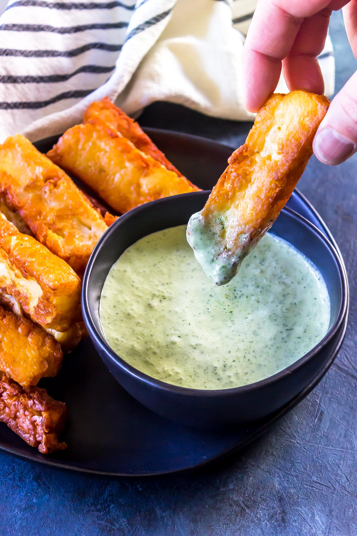 Keto Halloumi Fries being dipped into indian style yogurt based sauce