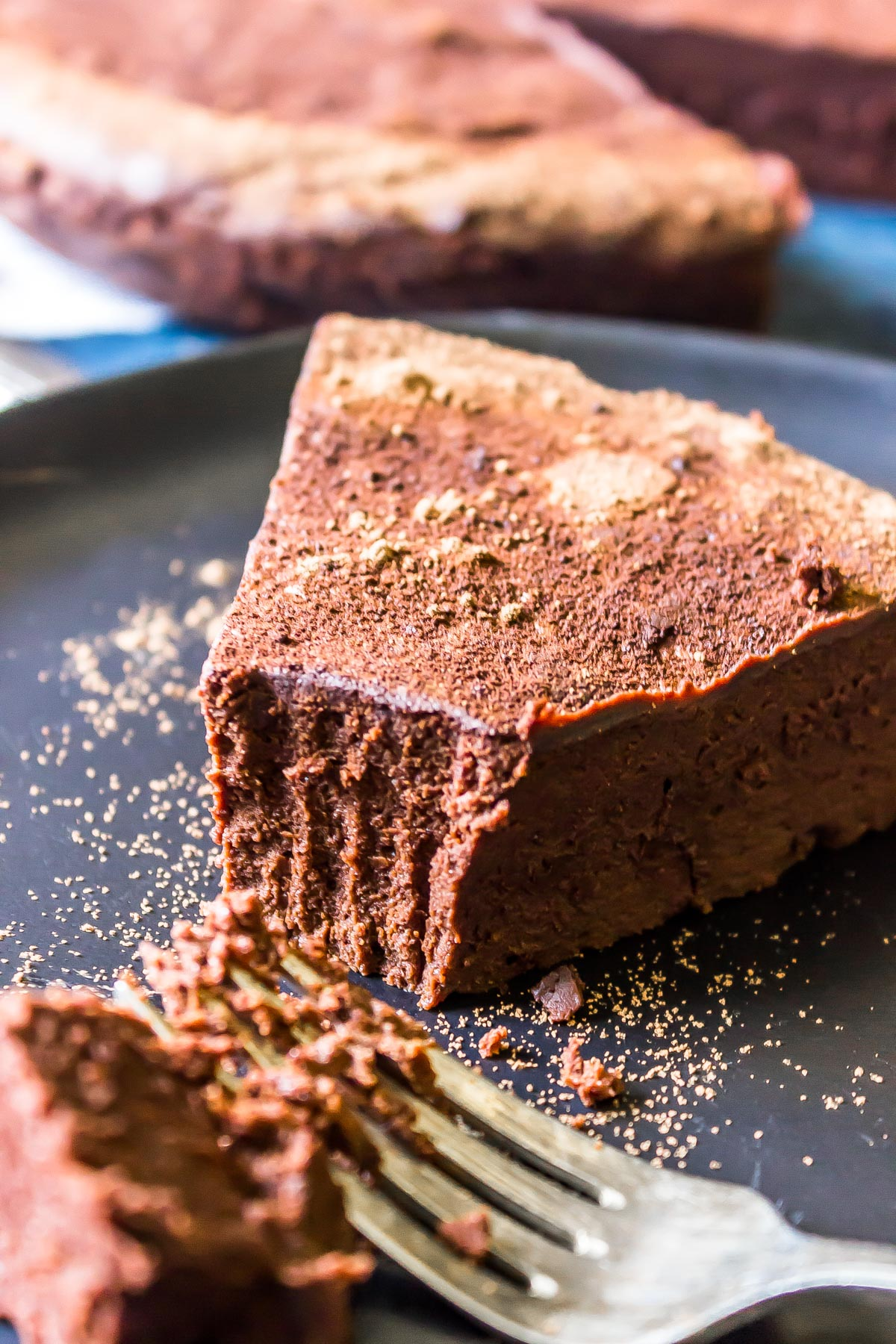 Flourless Chocolate torte with fork marks showing where a bite has been removed.