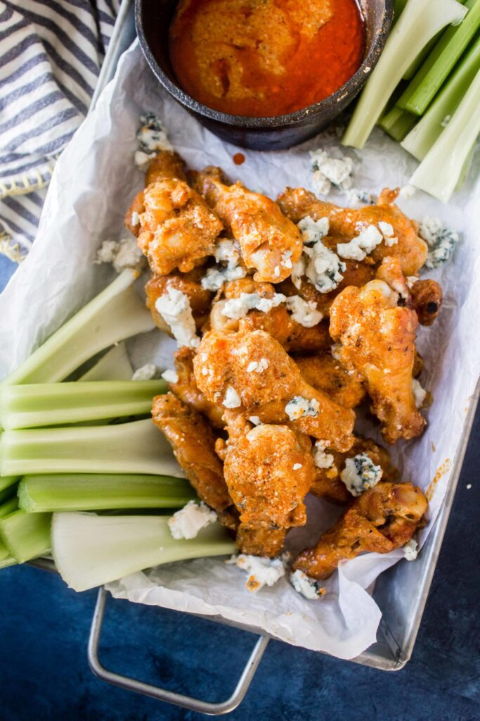keto chicken wings in tray with buffalo blue cheese sauce and celery