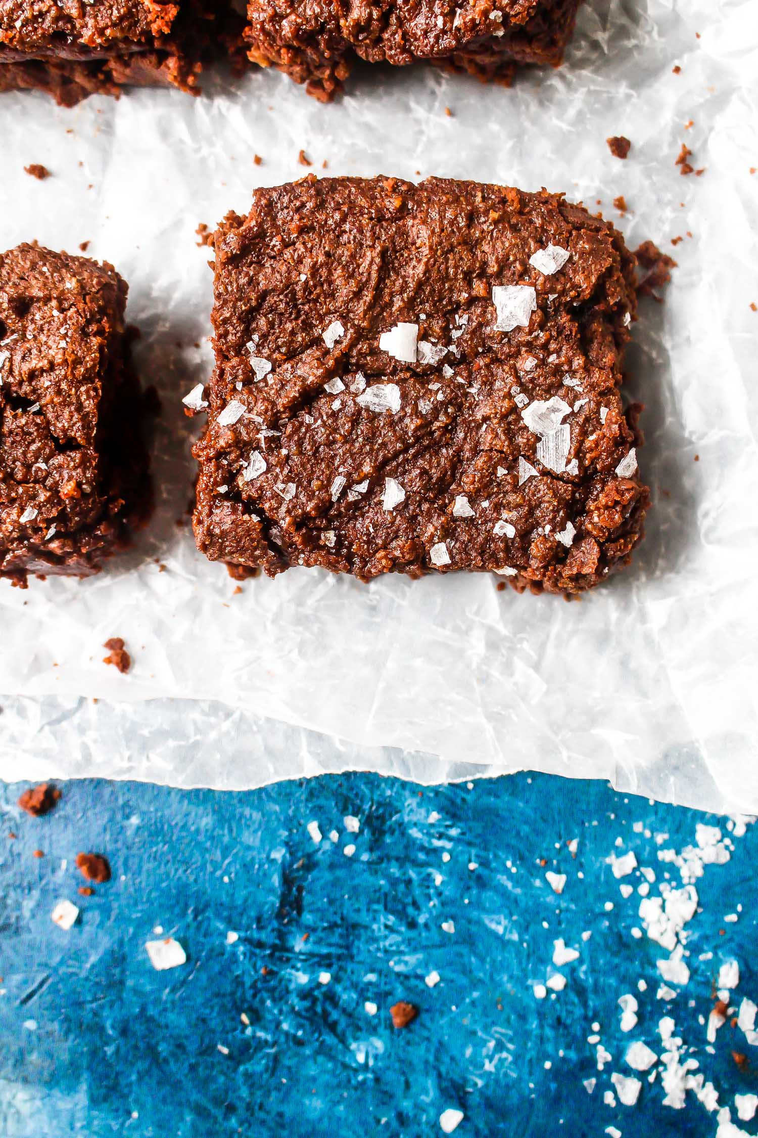 Brownie on white parchment with flaky sea salt sprinkled on top.