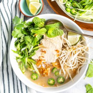 Keto Vietnamese Chicken Noodle Soup in bowl with a plate of toppings to the side