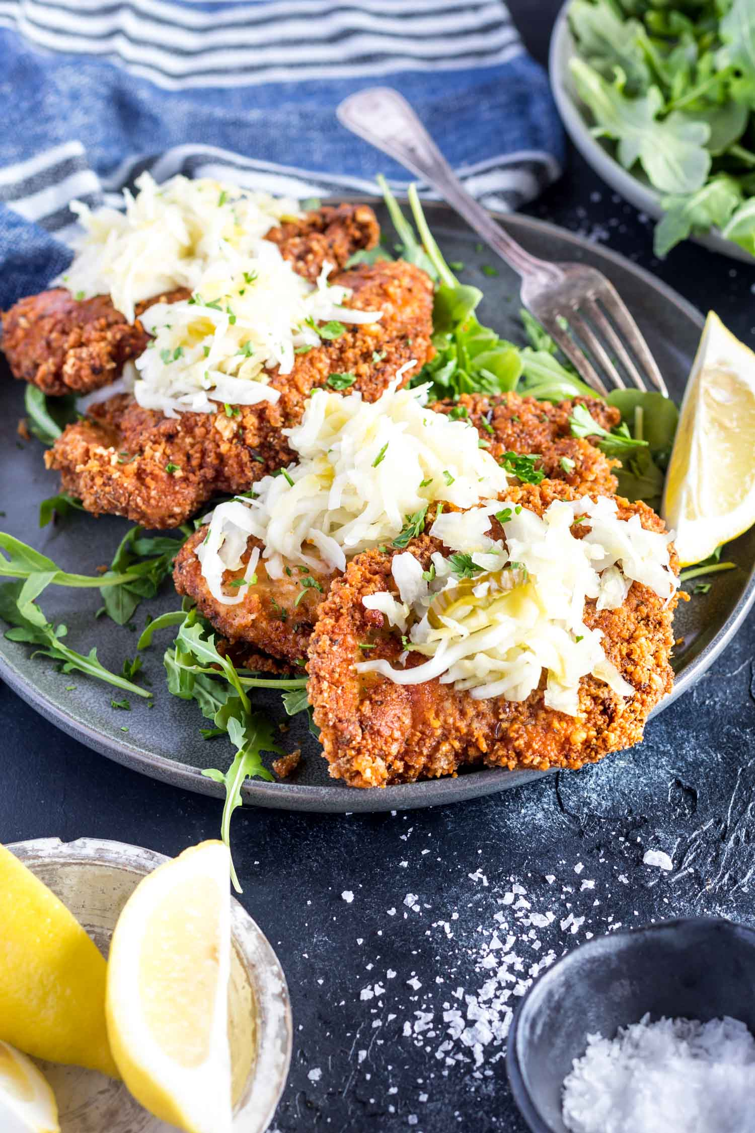 Keto Schnitzel on a plate topped with sauerkraut and served with arugula and lemon wedges
