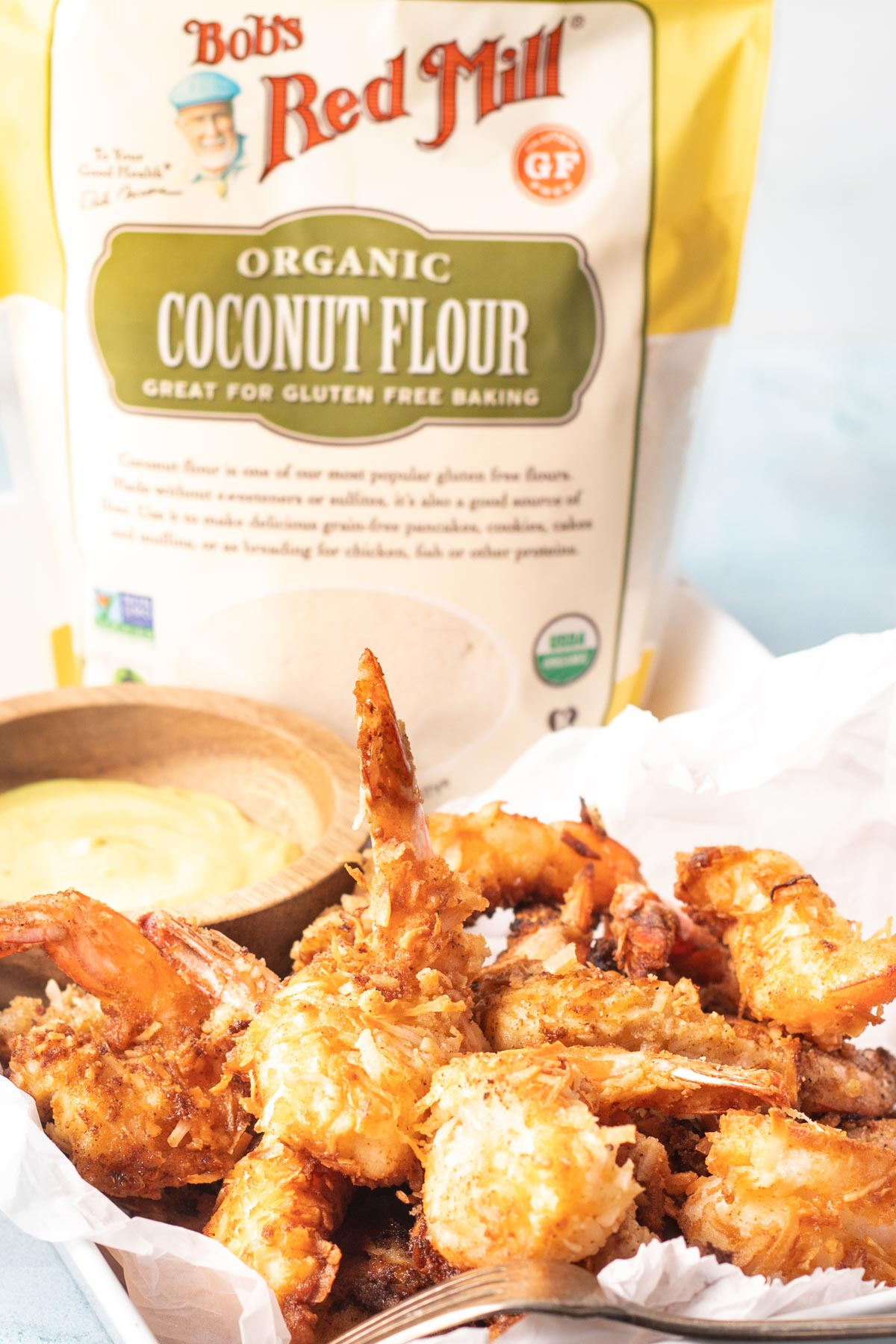 Keto Coconut Shrimp stacked in a serving tray with parchment paper, a wooden bowl of dipping sauce is in the background along with a package of Bob's Red Mill Coconut Flour.