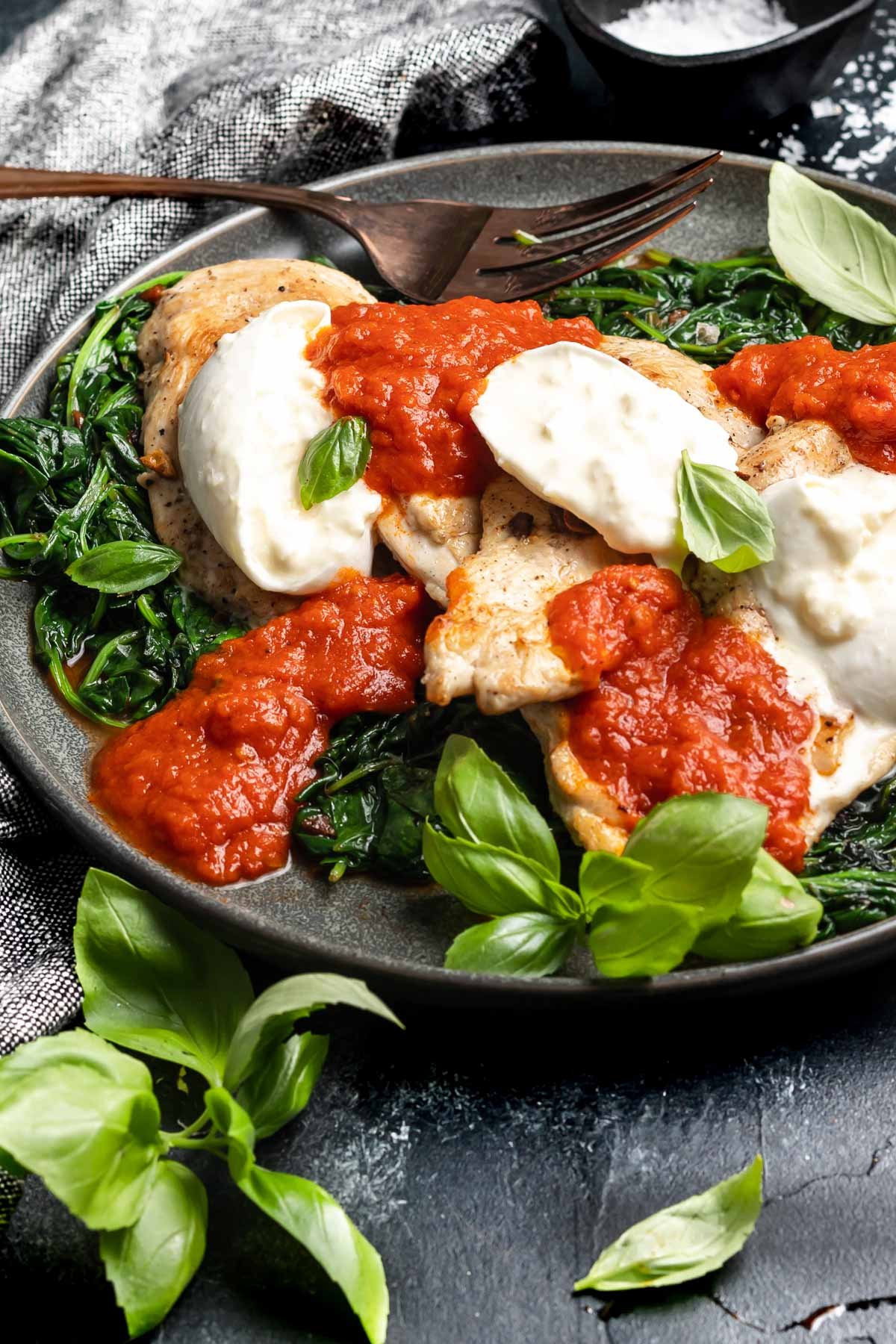 Cheesy Marinara Chicken on a plate on a black background with fresh basil leaves scattered around