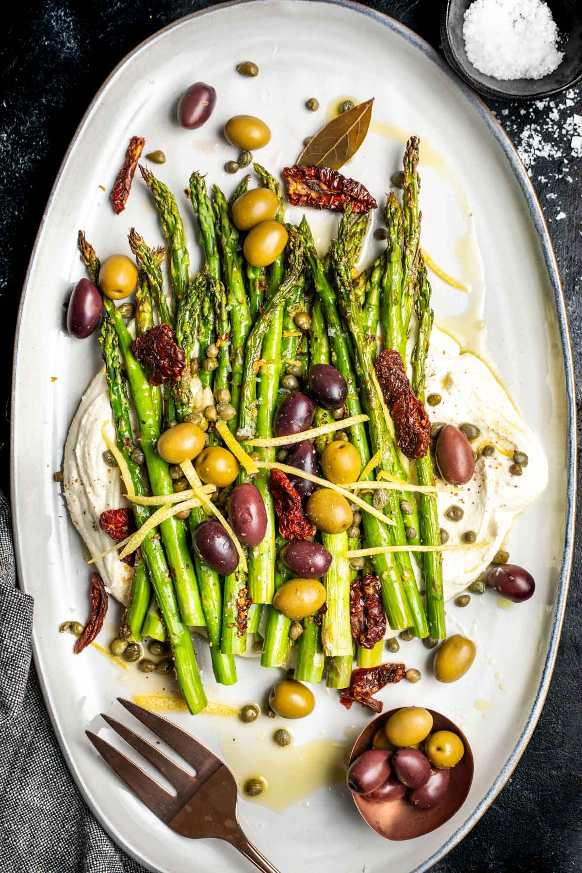 Mediterranean Asparagus - charred lemon garlic asparagus on top of whipped feta and topped with olives, capers, sun-dried tomatoes, and lemon zest.