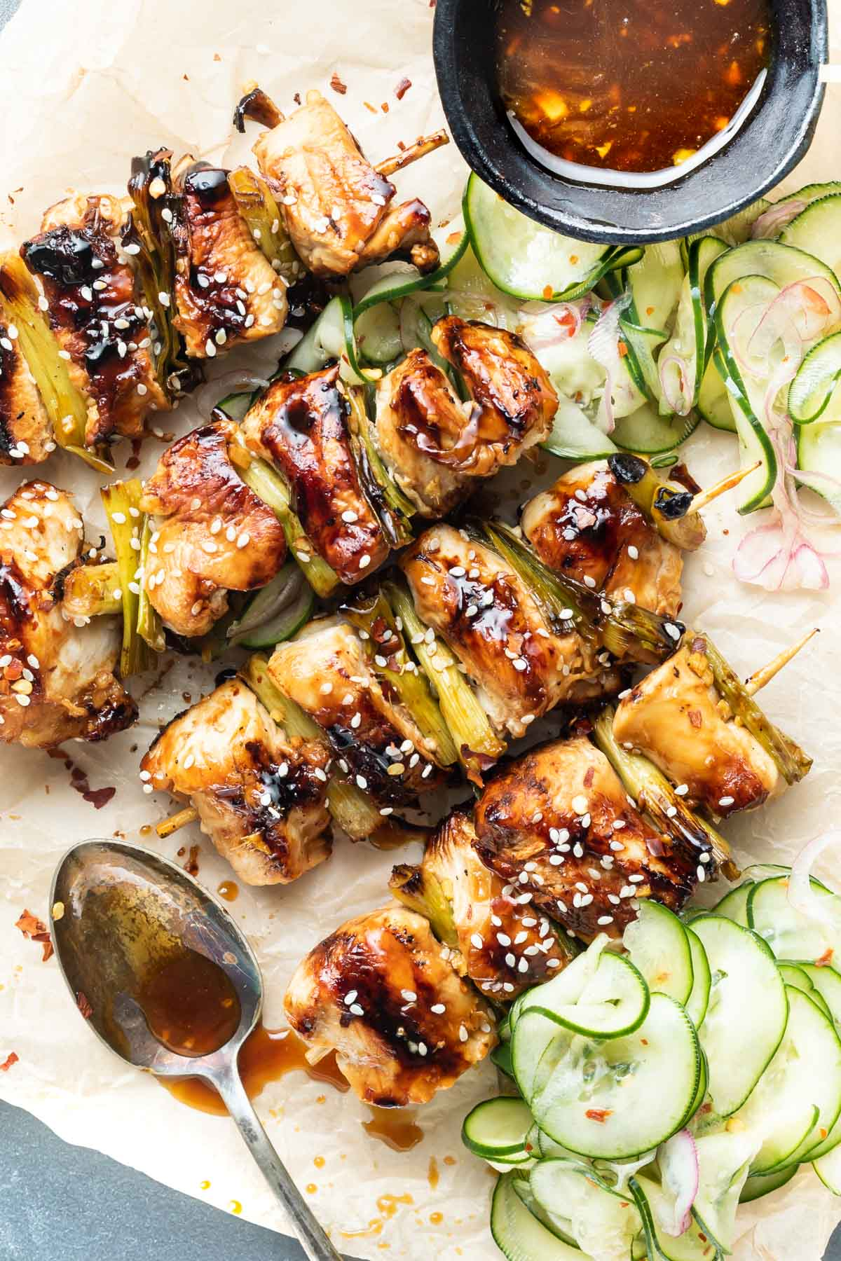 Keto Chicken Teriyaki Skewers with Pickled Cucumber Salad on a tray with a spoon splattering sauce over the top