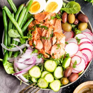 Keto Niçoise Salad in a bowl with a grey tea towel on black background
