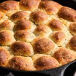 a side shot of a skillet full of seeded keto rolls