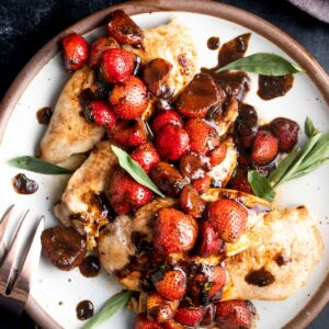 Strawberry Balsamic Tarragon Chicken on a plate with a bowl of strawberries in the background