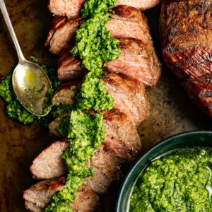sliced tri-tip steak on a platter drizzled with creamy avocado chimichurri