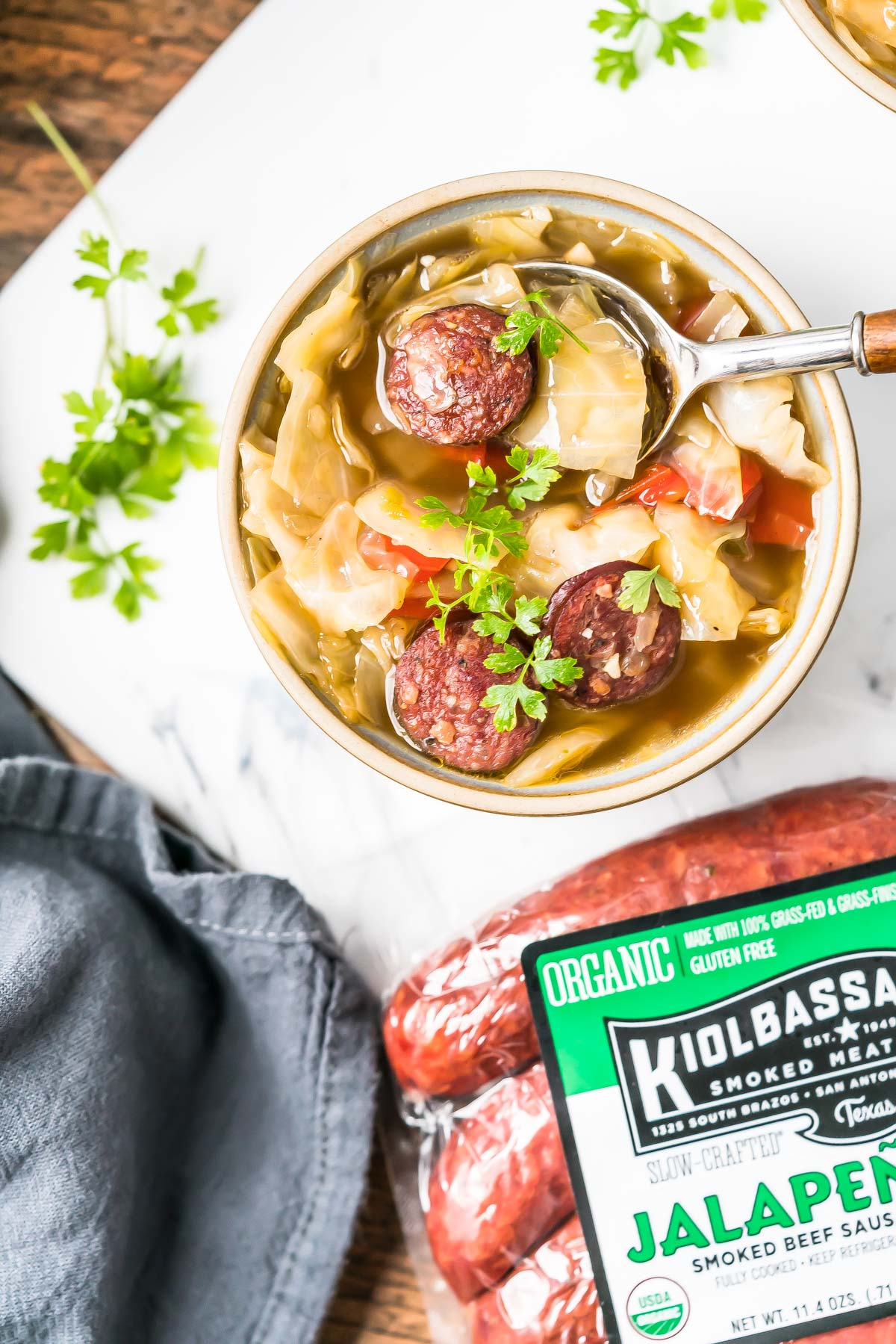Keto Cabbage Soup in a bowl with a package of Kiolbassa smoked sausages sitting next to it