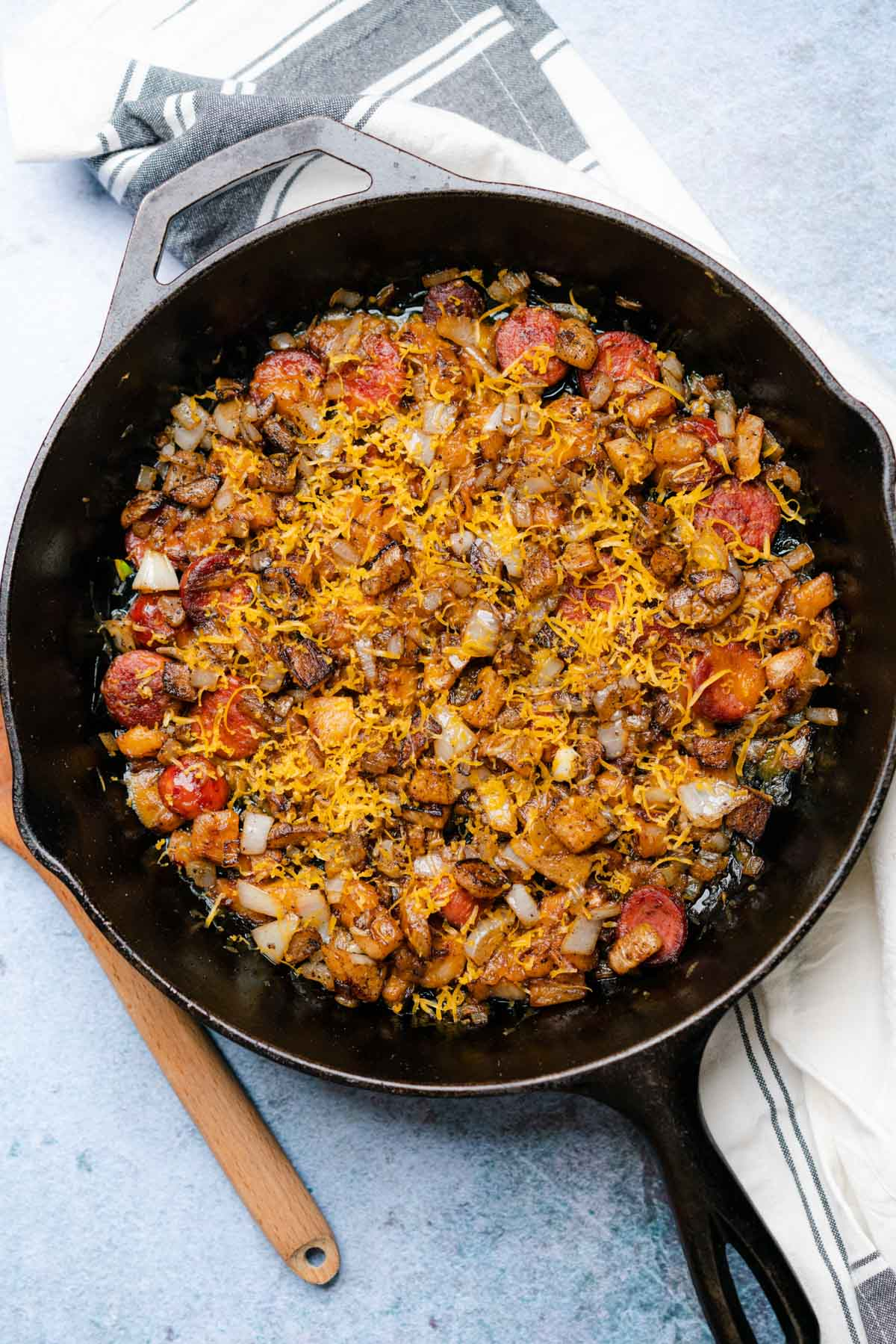 """Smoked Sausage Cheesy """"Potatoes"""" in a cast iron skillet being topped with shredded cheese"""