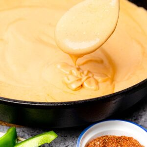 Keto Cheese Sauce in a cast iron skillet being scooped up with a spoon